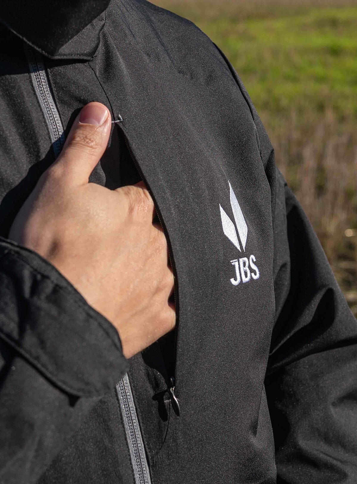 Strong, model-like male hand in left side of JBS Equipment jacket