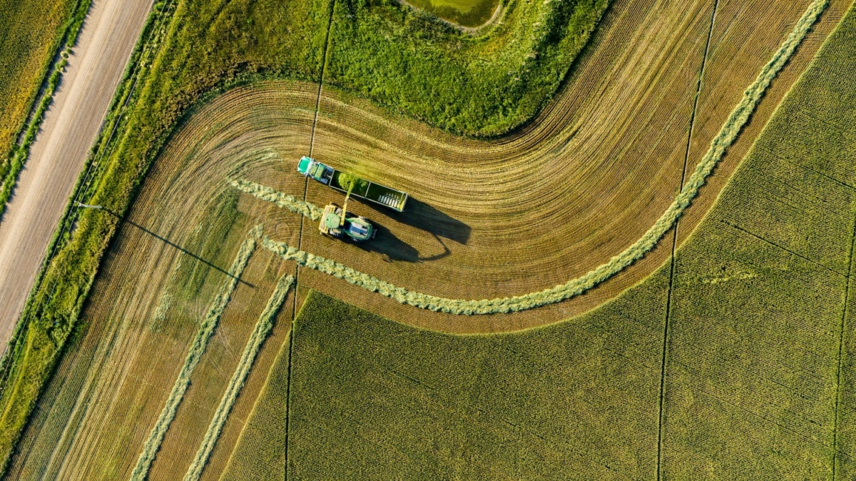 Two farm machines work in field shot by drone overhead
